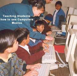 Merit students teaching students how to use computers in Mexico